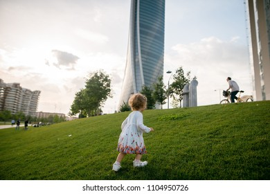 Rear view of cute liitle girl with blonde curly hair walking on the green lawn in the park near the skycrapers
