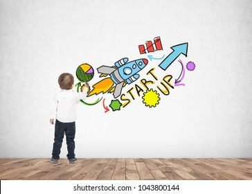 Rear view of a cute little boy wearing a white shirt and dark blue jeans writing or drawing with a marker. A concrete wall background with a start up sketch
