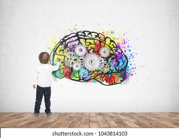 Rear view of a cute little boy wearing a white shirt and dark blue jeans writing or drawing with a marker. A concrete wall background with a cog brain sketch on it.