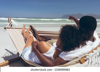 Vue arrière d'un mignon couple multi-ethnique se reposant sur un hamac tandis que des hommes afro-américains pointent vers quelque chose devant eux à la plage par beau temps