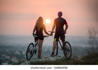 Rear view cyclist couple with mountain bikes standing on a rock holding hands enjoying the sunset. Bright sun in between. Blurred background