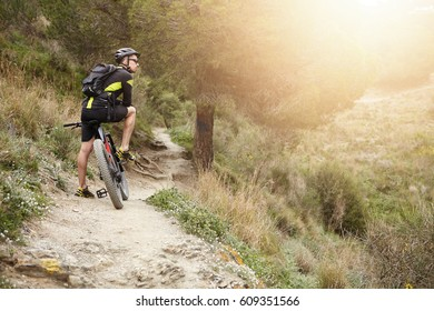 Rear view of cyclist standing on trail in forest with his motor-power e-bike resting during workout outdoors, feeling connected to nature, watching how sun goes down, thinking of his life. Flare sun