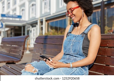 Rear view of dark skinned female holds modern cell phone, surfes fashion web site, listens music in earphones, dressed in ragged overalls and spectacles, models on bench, chats or reads text message