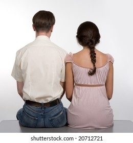 Rear view of dates sitting next to each other over white background