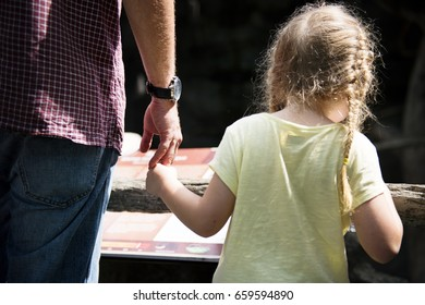 Rear view of daughter holding father hand