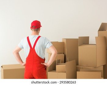 rear view of deliveryman standing, looking at cardboard boxes in front of him