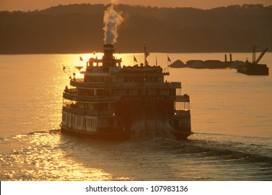 Rear view of The Delta Miss Queen steamboat on the Mississippi River at sunset