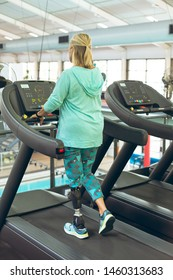 Rear view of disabled active senior Caucasian woman with leg amputee exercising on treadmill in fitness studio. Strong active senior female amputee training and working out