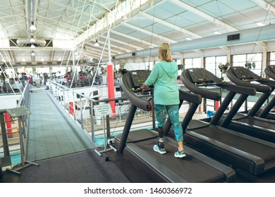 Rear view of disabled active senior Caucasian woman with amputee exercising on treadmill in fitness studio. Strong active senior female amputee training and working out
