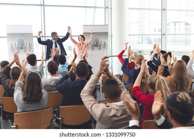Rear view of diverse business people applauding and celebrating while they are sitting in front of multi-ethnic business people at business seminar in office building