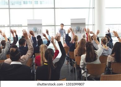 Rear view of diverse business people raising hands at business seminar while Asian businessman points at someone to give them a turn to speak
