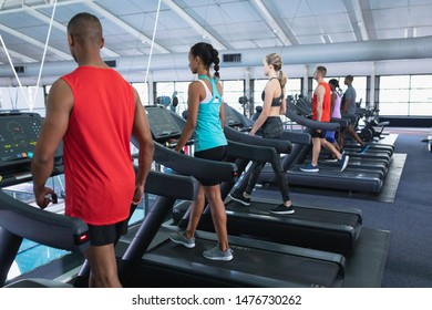 Rear view of diverse fit people exercising on treadmill in fitness center. Bright modern gym with fit healthy people working out and training