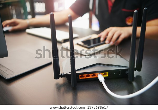 Rear view of Dual Band Router or Wireless AC router with business man using a computer in home office background . Computers and Router wireless broadband Accessories concept