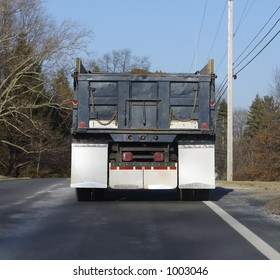 REAR VIEW OF DUMP TRUCK ON THE ROAD