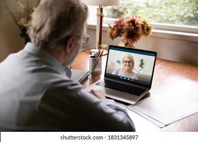 Rear view of elderly man speak talk on video call on laptop with smiling mature woman. Old husband have webcam digital conference with Caucasian middle-aged wife on computer. Virtual event concept.