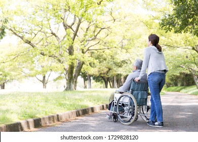 Rear view of elderly man in wheelchair and care helper