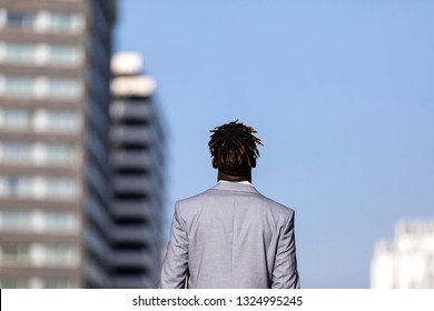 Rear view of a elegant black african young man standing against blue sky in the city while looking away to the horizon