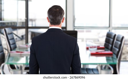 Rear view of an elegant businessman against empty corporate meeting room