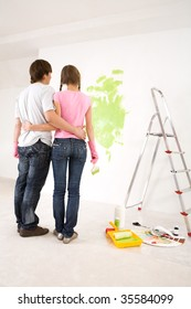 Rear view of embracing couple looking at wall with green paint on