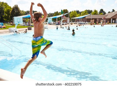 Rear view of energetic little Caucasian boy jumping in outdoor swimming pool. Boy resting at summer resort by hotel pool