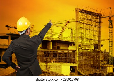 rear view of engineer pointing to the future building construction crane with beautiful sunset