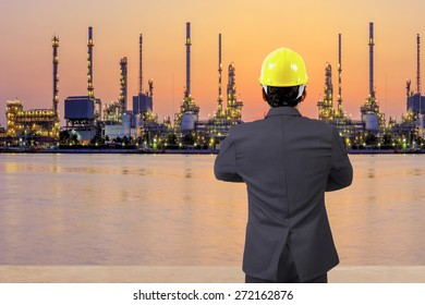 rear view engineer standing cross one's arm chest  at petrochemical oil refinery in sunrise
