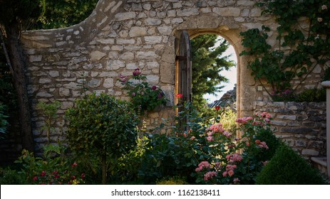 Rear view of a fairy like rose garden with an ancient stone wall and an open wooden door