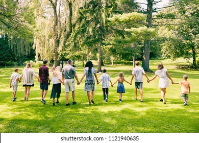 Rear view of family of eleven walking in park