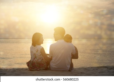 Rear view of family enjoying outdoor activity together, sitting on seaside in beautiful sunset during holiday vacations.