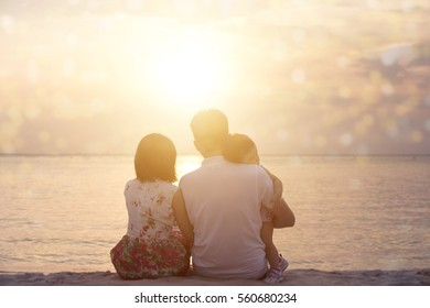 Rear view of family enjoying outdoor activity together, sitting on coastline in beautiful sunset during holiday vacations.