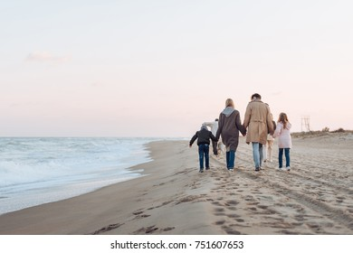 rear view of family holding hands and walking on sandy beach