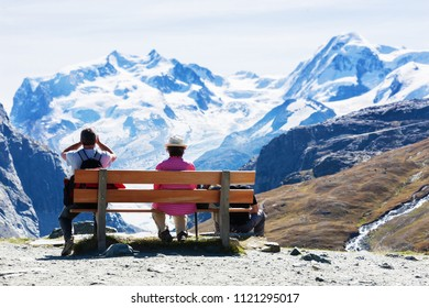 Rear view of family resting on the bench, looking at snowy mountains, senior couple and young man, unrecognizable people
