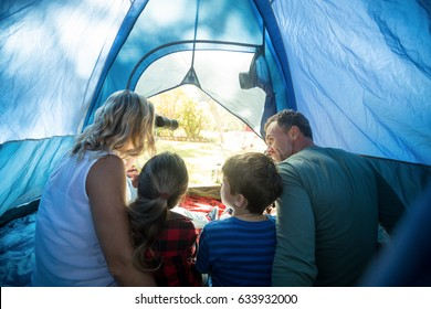 Rear view of family sitting in the tent