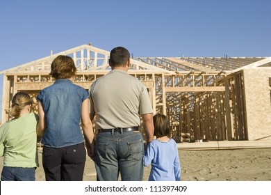 Rear view of family standing in front of incomplete house