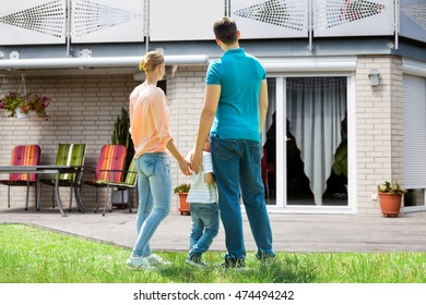 Rear View Of A Family Standing In Front Of Their New House