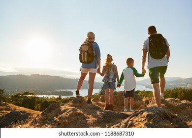 Rear View Of Family Standing At Top Of Hill On Hike Through Countryside In Lake District UK
