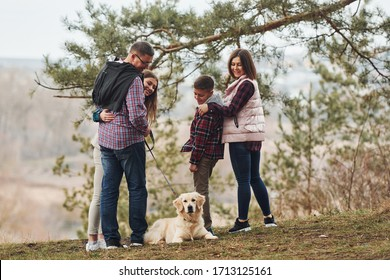 Rear view of family that standing together with their dog outdoors in forest.