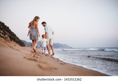 Rear view of family with two toddler children walking on beach on summer holiday.