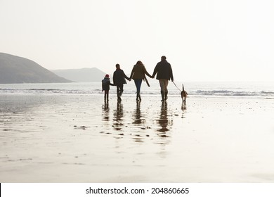 Rear View Of Family Walking Along Winter Beach With Dog