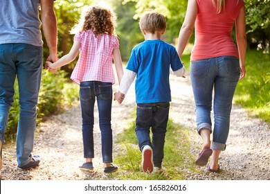 Rear View Of Family Walking In Countryside