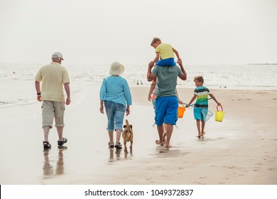 Rear view of a family walking to the sea front while on holiday at the seaside.