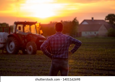 Rear view of farmer looking at tractor working in field in spring at sunset