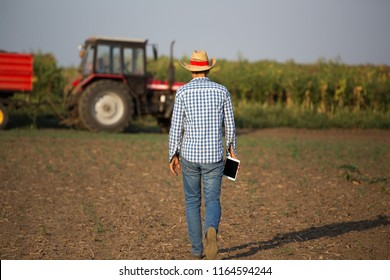 Rear view of farmer with tablet and straw hat in front of tractor with trailer in field