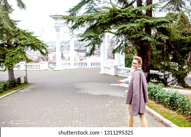 rear view of fashion woman with coat walkin a strret park