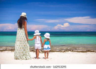 Rear view of fashion young mother and two her kids at exotic beach on sunny day