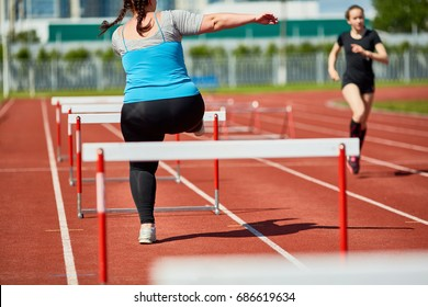 Rear view of fat woman in sportswear running on stadium and overcoming obstacles