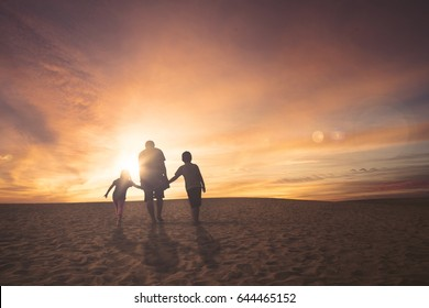 Rear view of father and children walking together on the sand at sunset time
