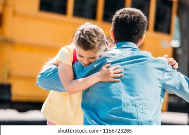rear view of father and daughter embracing in front of school bus