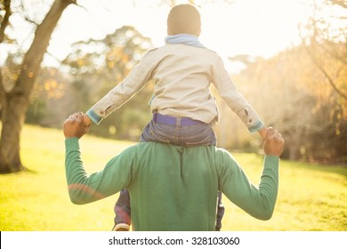 Rear view of a father with his son in piggyback on an autumns day