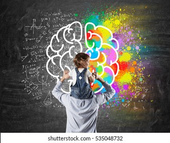 Rear view of a father with his son on the shoulders standing near a blackboard with a colorful brain sketch. Concept of early development